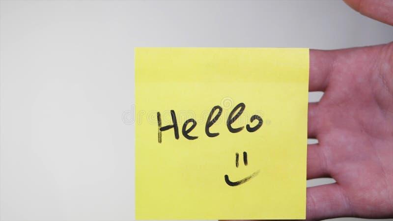 与词的贴纸你好在玻璃 你好-在纸备忘录,企业概念的题字 库存图片