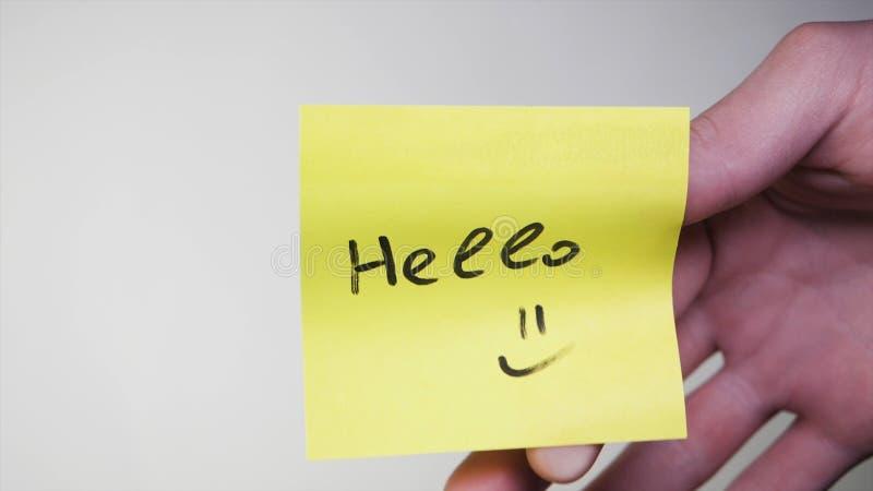 与词的贴纸你好在玻璃 你好-在纸备忘录,企业概念的题字 免版税库存图片