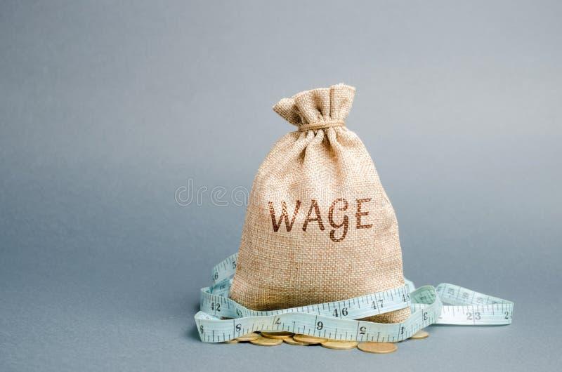 与词薪水和卷尺的金钱袋子 工资削减 有限的赢利的概念 缺钱和贫穷 小收入 库存照片