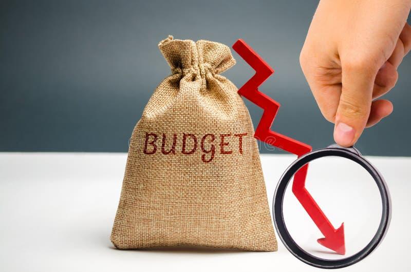 与词预算和下来箭头的金钱袋子 不成功的事务和贫穷 赢利衰落 投资损失  低工资和 免版税库存图片