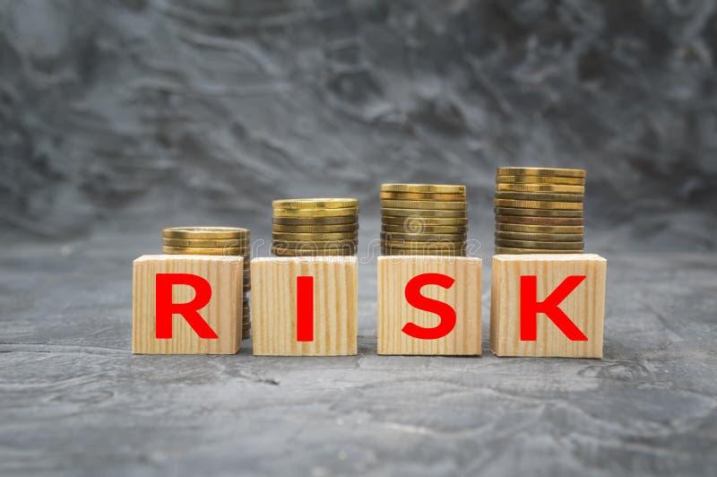 与词风险和金钱硬币堆的木块在黑暗的背景 财政债务减退概念 免版税库存图片