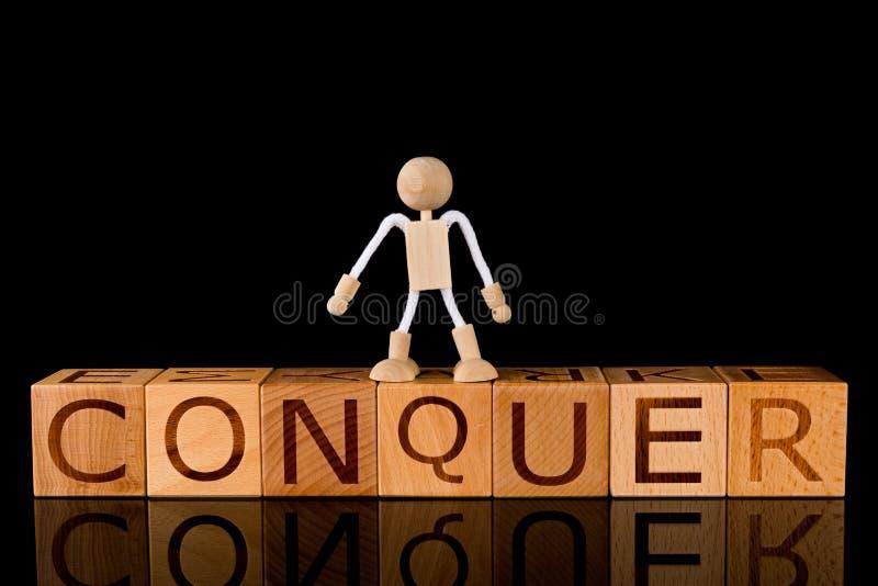 """与词""""CONQUER†的木立方体块和在黑背景的木棍子形象身分 免版税库存图片"""