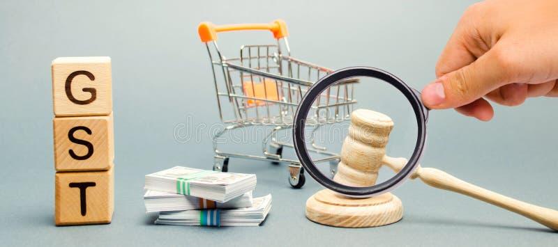 与词GST,金钱和一辆超级市场台车的木块有法官的惊堂木的 税,被征收给物品销售  图库摄影
