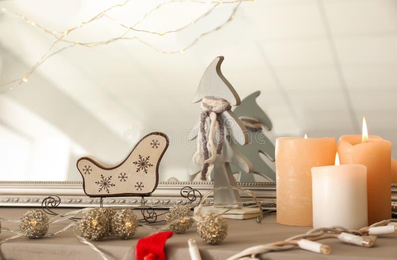 与诗歌选的燃烧的蜡烛在为圣诞节装饰的壁炉架 免版税库存照片