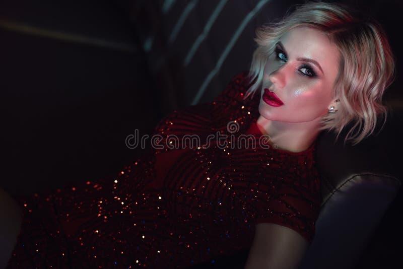 与诱惑的美好的迷人的白肤金发的模型在沙发做放松佩带的红色衣服饰物之小金属片的礼服在夜总会 库存照片