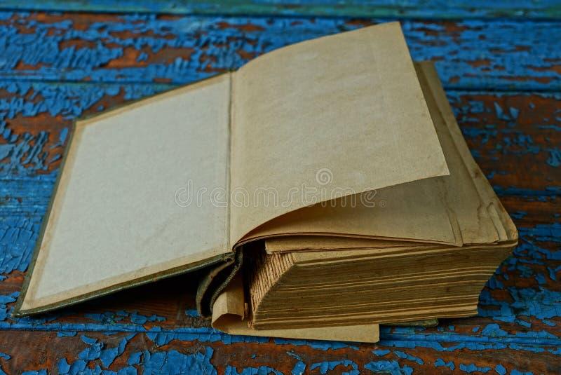 与说谎在一张蓝色,破旧的木桌上的灰色棕色页的开放旧书 免版税库存照片