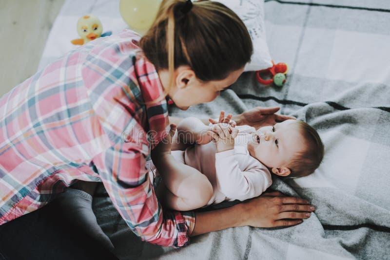 与说谎在地毯的逗人喜爱的婴孩的年轻母亲戏剧 免版税图库摄影