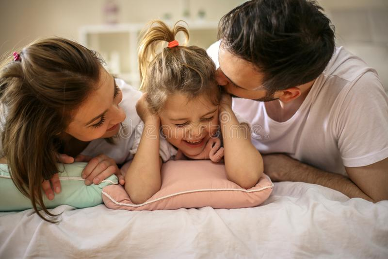 与说谎在床上的一个女儿的家庭 免版税库存照片