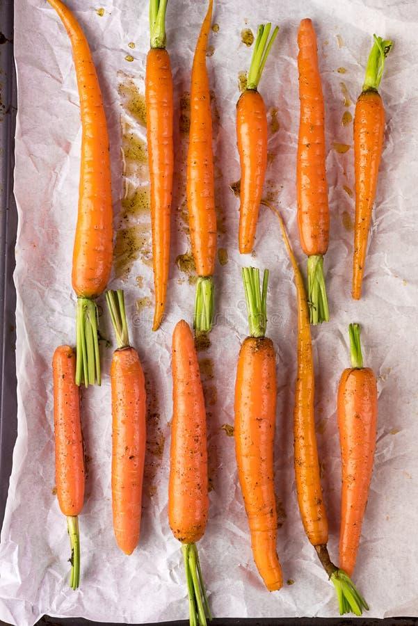 与说谎在烘烤的盘子的橄榄油和香料的未加工的Freah红萝卜准备好烹调顶视图水平的健康饮食有机食品 免版税库存照片