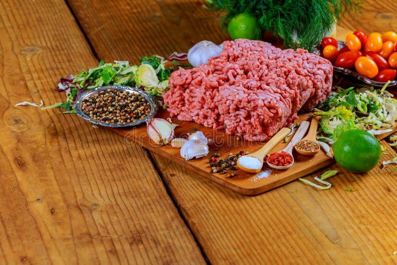 与调味料的未加工的绞细牛肉肉汉堡牛排炸肉排,蕃茄, 免版税库存照片