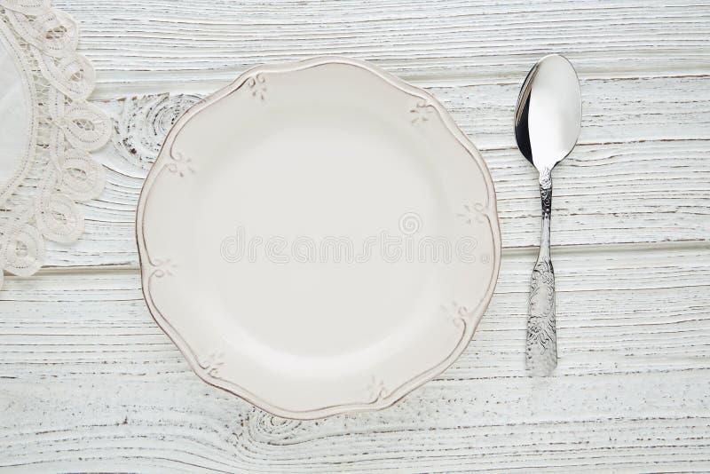 与调羹食品饥饿的概念的空的板材盘 免版税库存照片