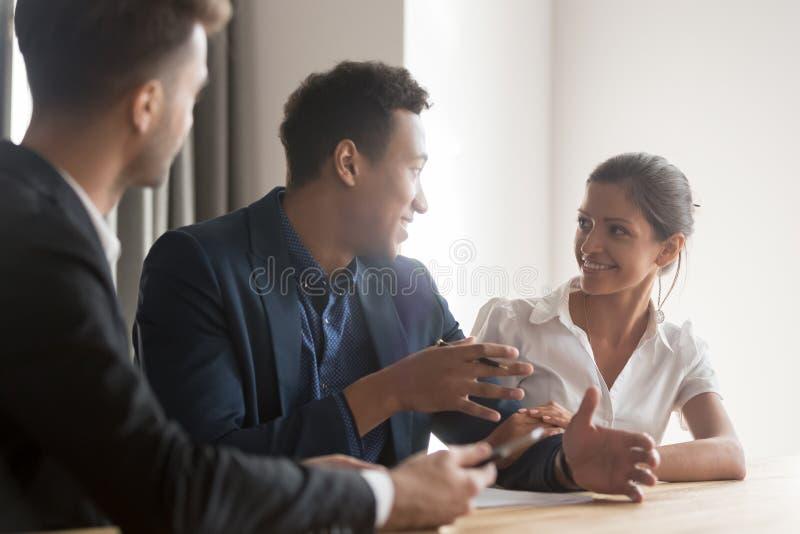 与谈论的顾问的微笑的不同的夫妇会议购买 库存图片