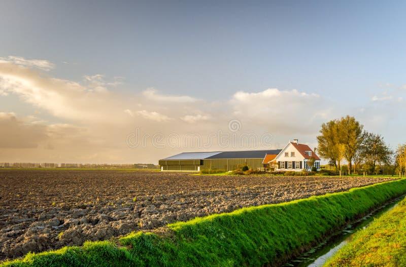 与谷仓的现代荷兰农舍黄昏光的 库存照片