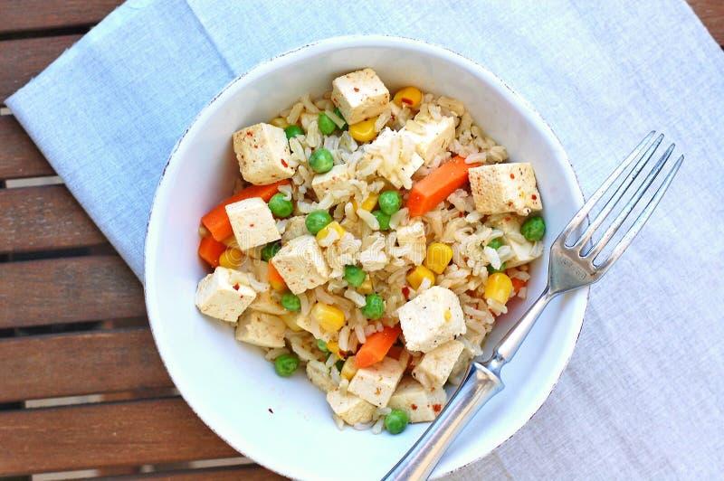 与豆腐、豌豆、红萝卜、甜玉米和整个五谷米的健康素食主义者膳食 免版税图库摄影