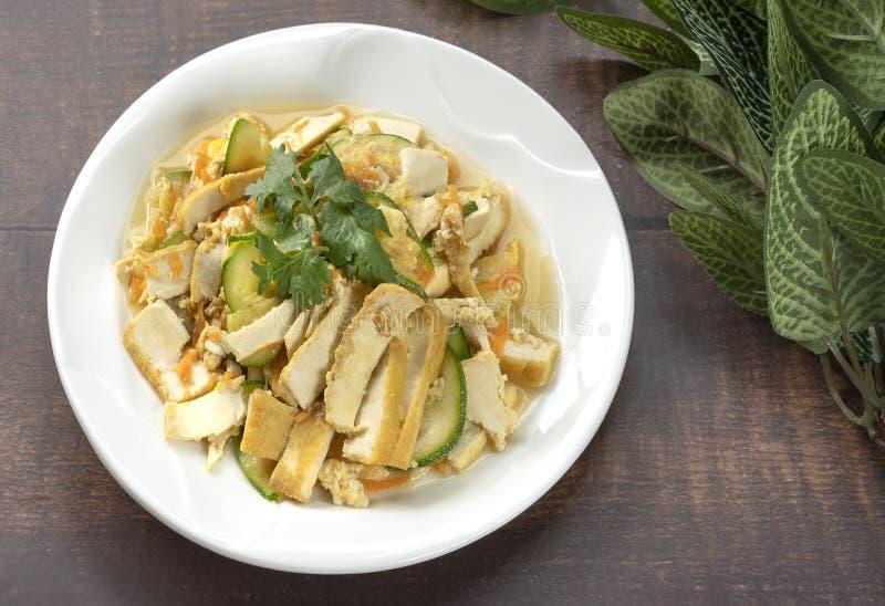 与豆腐和鸡蛋的油煎的夏南瓜在白色陶瓷板材,vega投入了 免版税库存图片