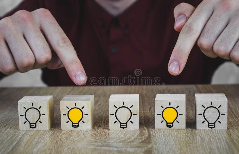 与象征一个新的创新的想法、概念和解答一个电灯泡,其中2捅a的图象的木立方体 免版税图库摄影