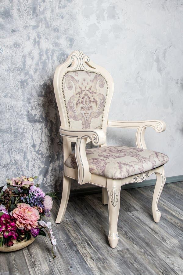 与豪华扶手椅子的古板的内部在茶黄墙纸背景 库存图片