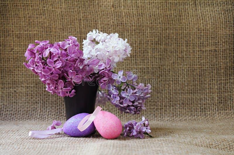 与豪华的淡紫色花的复活节静物画在陶瓷花瓶和de 免版税图库摄影
