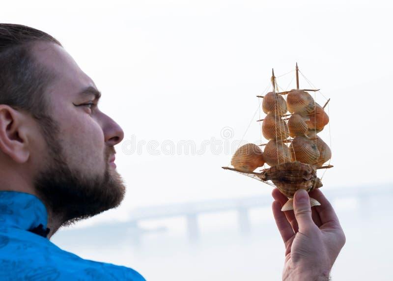 与贝壳的船模在河前面的有胡子的人手上 库存图片