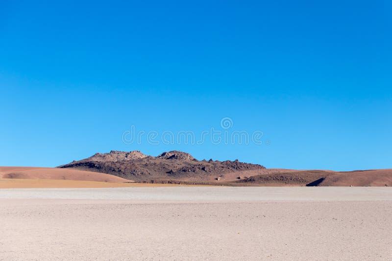 与贫瘠沙漠风景的背景在自然保护的Edoardo Avaroa玻利维亚人安地斯, 图库摄影