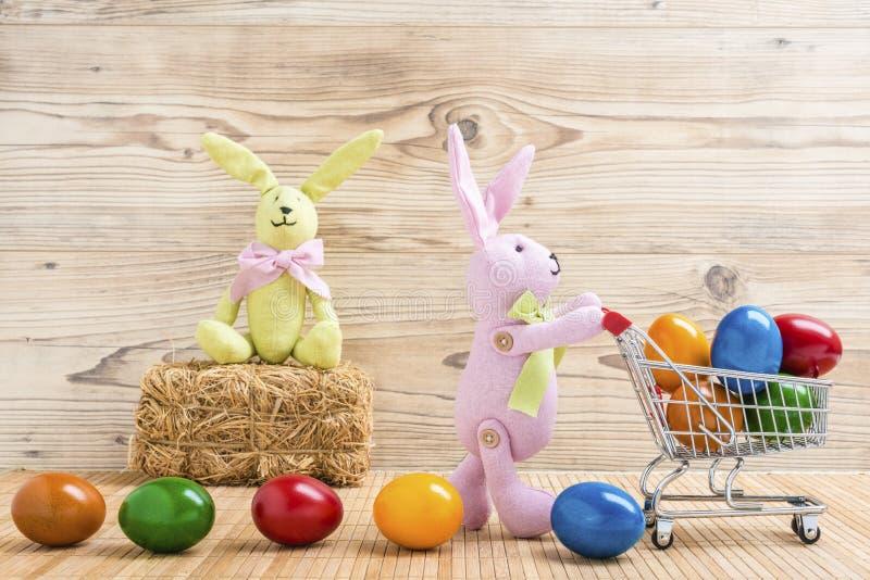 与购物车和许多五颜六色的复活节彩蛋的两只复活节兔子 免版税库存照片