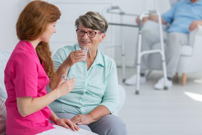与资深妇女的护士饮用水 免版税库存照片
