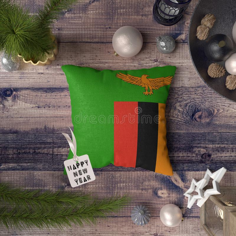 与赞比亚旗子的新年快乐标记在枕头 在木桌上的圣诞装饰概念与可爱的对象 免版税库存照片