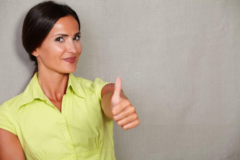 与赞许和微笑的愉快的成年女性 库存照片
