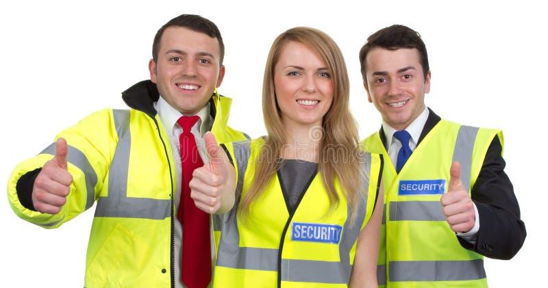 与赞许的三名治安警卫在白色签字,隔绝 免版税图库摄影