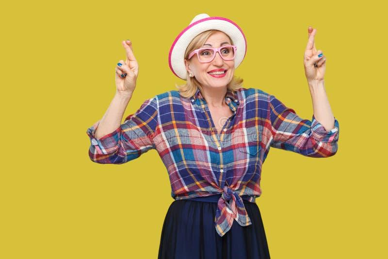 与赢得 有希望的喜悦的现代时髦的成熟妇女画象便装样式的与与横渡的帽子和镜片身分 免版税库存照片