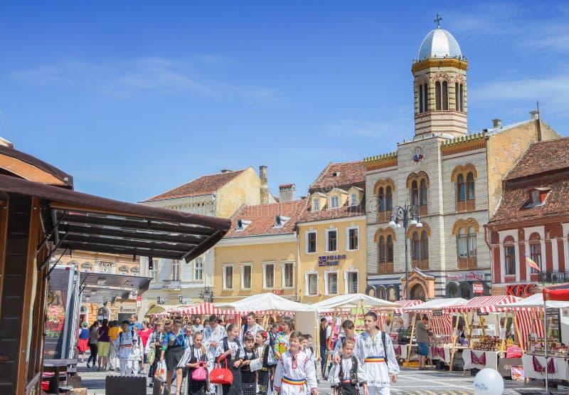与走在理事会正方形(Piata Sfatului),与市政厅的地标的民间服装孩子的风景中世纪布拉索夫的 库存图片