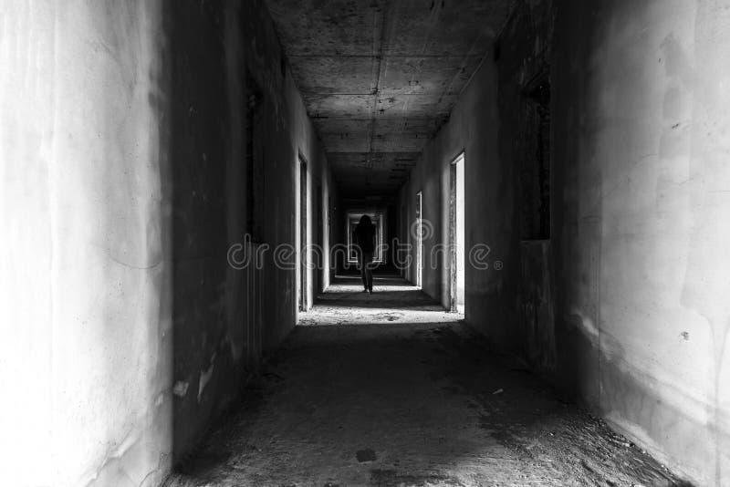 与走在wallway的鬼魂的被放弃的大厦 库存照片