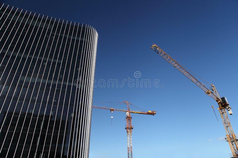与起重机和玻璃摩天大楼的建设中站点大厦 免版税库存照片