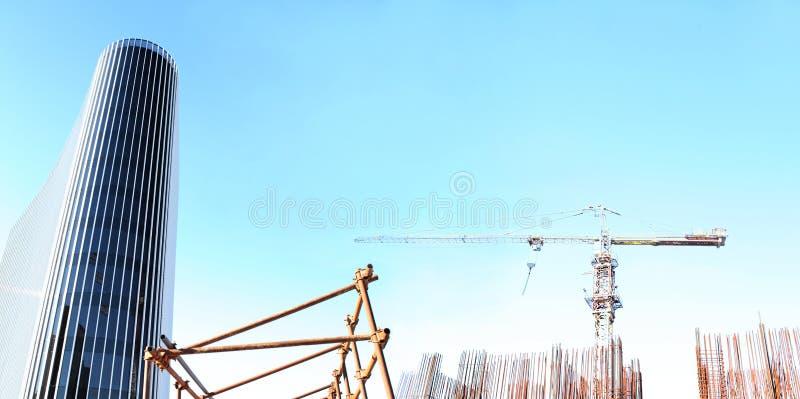与起重机和玻璃摩天大楼的建设中站点大厦 库存照片
