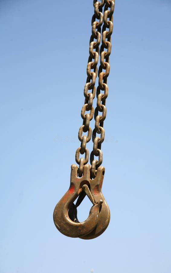 与起重机的长的生锈的链子钩作为工业背景 库存照片