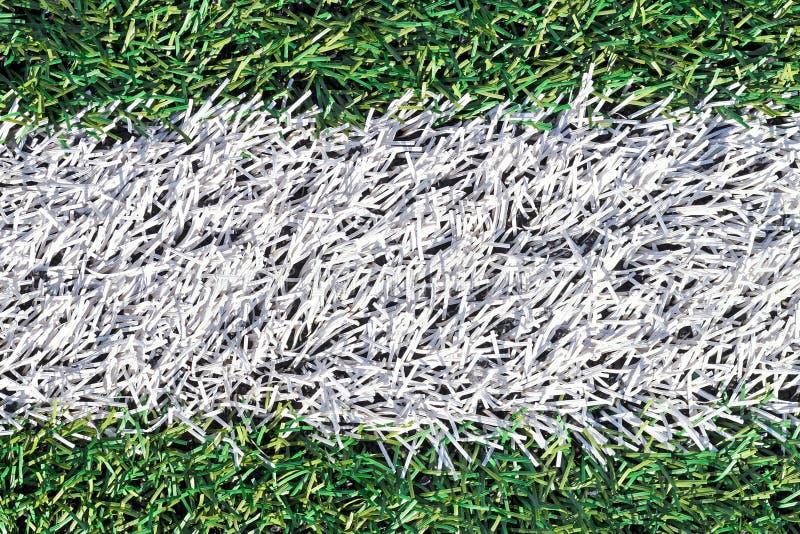 与足球场白色条纹的人为绿草  库存图片