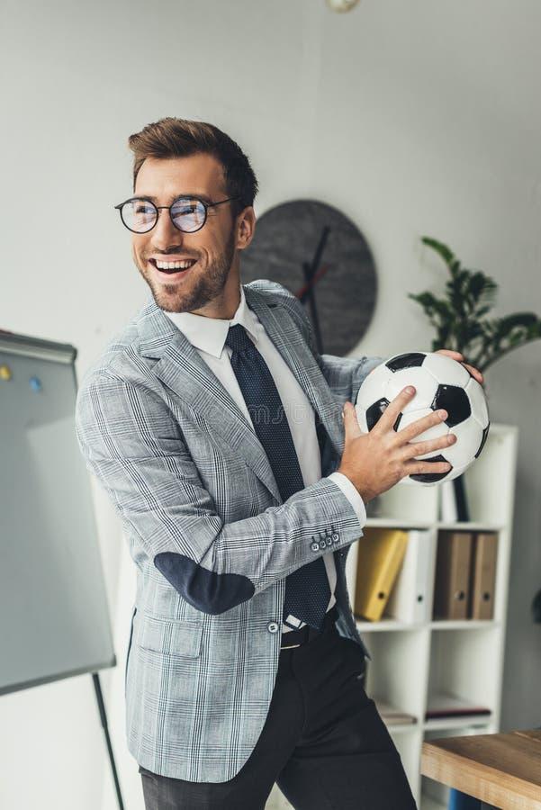 与足球的年轻愉快的商人 免版税库存照片
