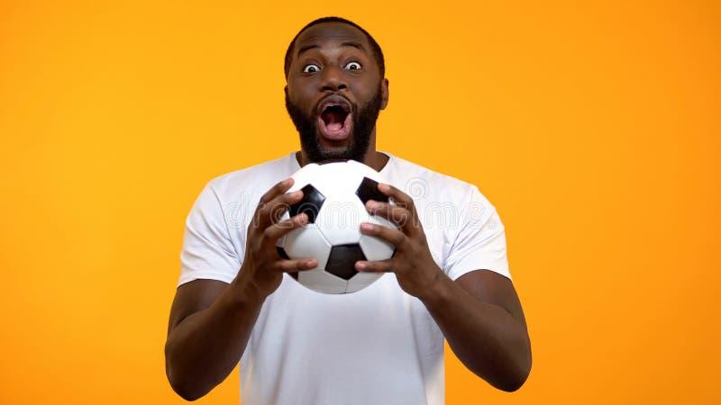 与足球的年轻美国黑人的男性情感地欢呼为国家队的 库存图片