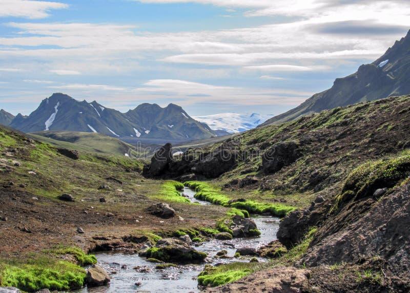 与跑从米达尔斯冰原冰川,Hvanngil,Laugavegur足迹,冰岛的高地的冰河河的火山的风景 图库摄影