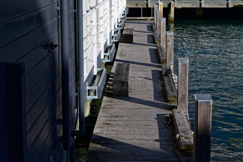 与跑沿码头的木柱子的木江边步行方式 图库摄影