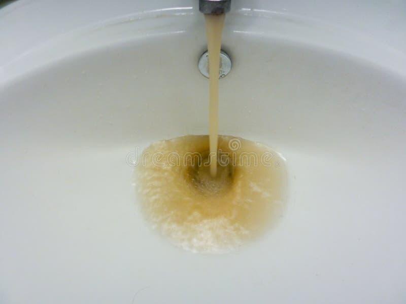 与跑肮脏的泥泞的水的水龙头在水槽 库存照片