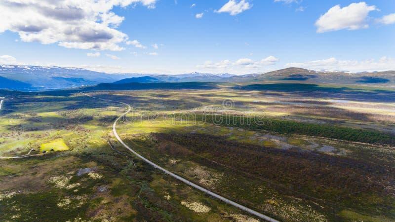 与路、山和蓝天,从寄生虫的空中射击的挪威风景视图 免版税图库摄影