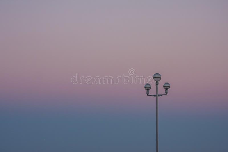 与路灯柱的日落 库存照片