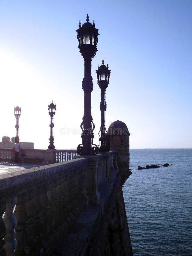 与路灯柱的海岸在日落在卡迪士 库存照片