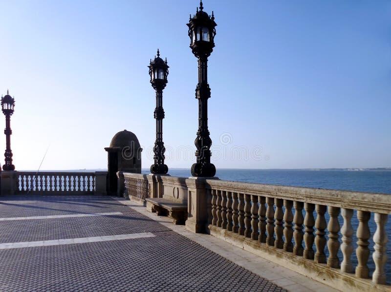 与路灯柱的海岸在日落在卡迪士 免版税图库摄影