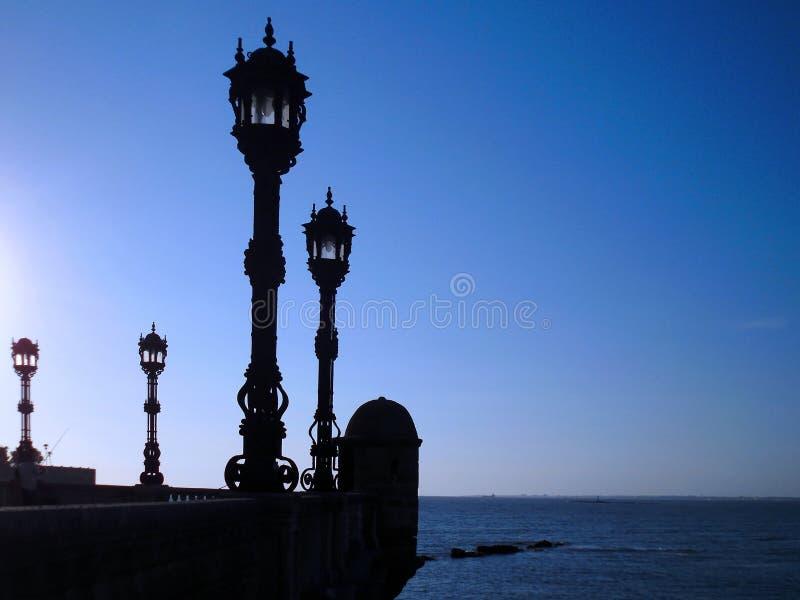 与路灯柱的海岸在日落在卡迪士 图库摄影