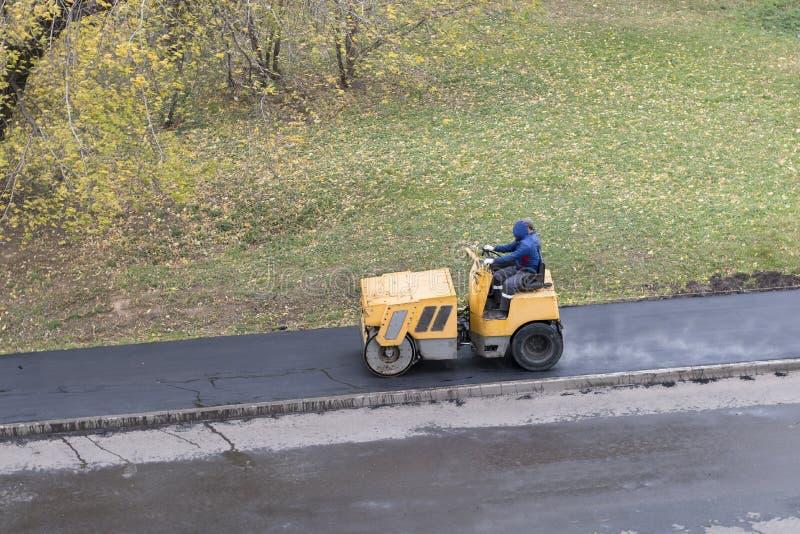 与路辗压紧机机器的修路工作者compactes新鲜的通入蒸汽的沥青 免版税图库摄影