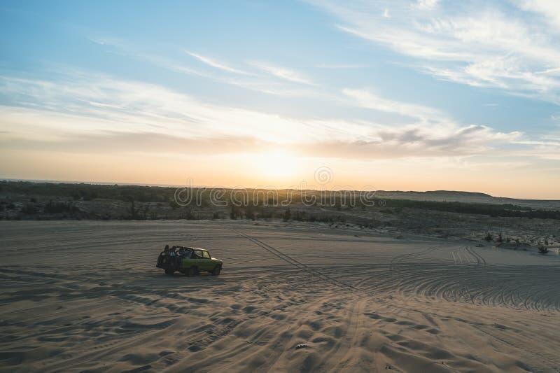 与路4x4汽车的沙漠徒步旅行队在阳光下 五颜六色的日落在沙漠 在沙子的越野汽车乘驾在沙漠沙丘 库存照片