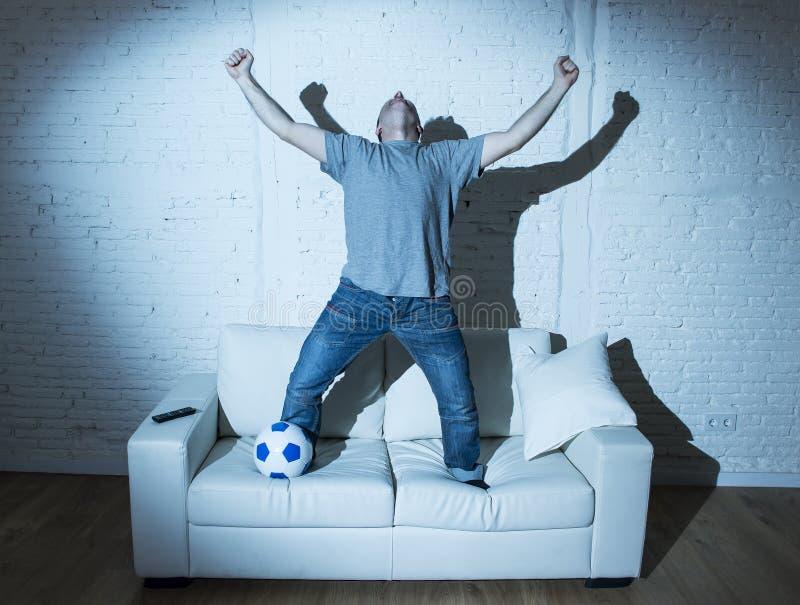 与跳跃在沙发的球的狂热和疯狂的足球迷观看的电视足球比赛庆祝目标 图库摄影