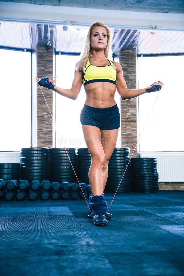 与跳绳的年轻逗人喜爱的运动的妇女锻炼 免版税库存图片